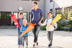 Mum e crianças com funis de papel para doces após o primeiro dia em Imagens de Stock Royalty Free