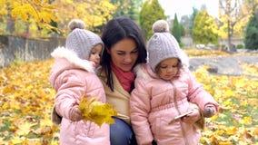 Mum e duas filhas no parque que olha o telefone no au vídeos de arquivo