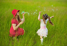 Mum e filha que começam acima das bolhas de sabão Fotografia de Stock