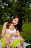 Mum embraces the daughter. Sitting on the grass Royalty Free Stock Photos
