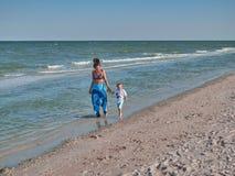 Mum en de zoon lopen langs het strand De jonge moeder met jong geitje weinig jongen is op de kust Gelukkige familie en gelukkig stock foto