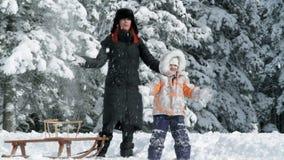Mum en dochter die van sneeuw de wintertijd genieten stock footage