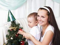 Mum en haar dochter verfraaien een Kerstmis bont-boom Stock Afbeeldingen