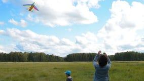 Mum en zoons vliegende vlieger openlucht stock footage