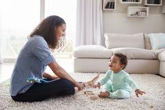 Mum för blandat lopp och litet barnson som spelar i vardagsrum royaltyfria foton