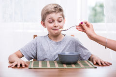 Mum feeding picky eater Stock Image
