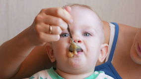 Mum feeds the beautiful baby with a spoon fruit porridge. The child looks at one point carefully. Close-up stock footage