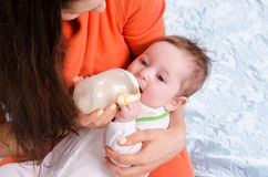 Mum feeds from a bottle six-month baby girl. Six month old baby drinking milk from a bottle with a nipple, lying on his mother's arms stock images