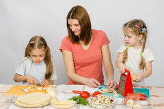 Mum with a five-year daughter watched as eldest daughter cutting mushrooms pizza. Mum with a five-year daughter watched as the eldest daughter cutting mushrooms Royalty Free Stock Photography