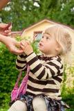 Mum geeft aan een dochterlippenstift openlucht Stock Afbeeldingen