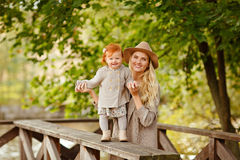 Mum gently embraces the redhead baby girl and laughing in autumn Stock Photo