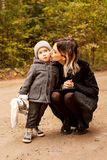 Mum gently kisses her little son on the path in the woods royalty free stock photo