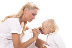 Mum giving a spoon of syrup to little girl Stock Photography