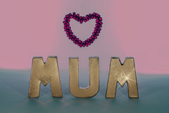 Mum in gold letters with pink love heart frame. Pastel colors. Stock Photos