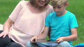 Mum grávido que joga o jogo na tabuleta com filho, maternidade feliz, planeamento familiar filme