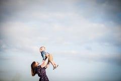 Mum heft een kind in zijn wapens tegen de hemel op Royalty-vrije Stock Foto