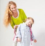 Mum helps her daughter get ready for school Stock Photo