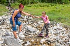 Mum helpt haar dochter om een bergstroom te kruisen stock fotografie