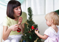 Mum and her daughter decorate a christmas fur-tree Royalty Free Stock Images