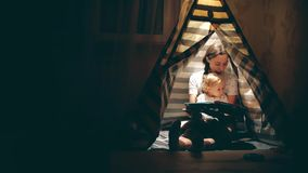 Mum and her little daughter read a book together in a teepee in the evening. Mum and her little daughter read a book together in a teepee stock footage