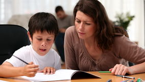 Mum and her son doing homework stock video footage