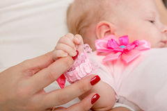 Mum holds the handle of his two-month daughter royalty free stock photo