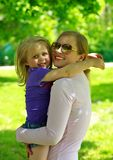 Mum holds the small daughter outdoors Royalty Free Stock Image