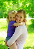 Mum holds the small daughter outdoors Royalty Free Stock Photo