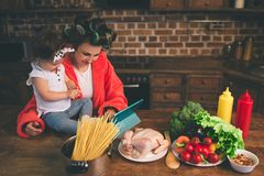 Mum at home. Young mother with little child in the home kitchen. Woman doing many tasks while looks after her baby. Use stock images