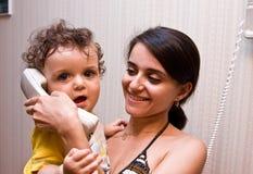 Mum houdt op handen het kind dat spreekt Stock Afbeelding