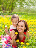 Mum and kid girl child among yellow flowers dandelions Royalty Free Stock Images