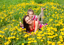 Mum and kid girl child among yellow flowers dandelions Royalty Free Stock Photos