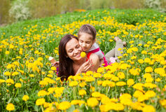 Mum and kid girl child among yellow flowers dandelions Stock Image