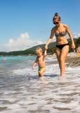 Mum with kid go near sea edge Stock Image