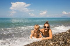 Mum with kid lie in sea waves Stock Photos