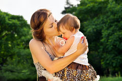 Mum kisses the baby on nature Royalty Free Stock Photography