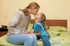 Mum kisses a daughter before a dream, sitting on the bed in room royalty free stock images