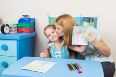 Mum kisses the daughter because she drew her beautiful royalty free stock photo