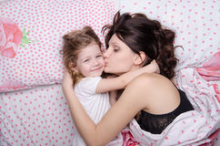 Mum kisses the daughter lying in bed royalty free stock image