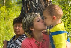 Mum kisses the son. The grandmother looks Stock Photography