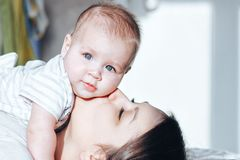 Mother kissing her little baby. Mum kissing her baby on a white bed. Newborn looking at the camera. Happy motherhood concept, mother`s day Stock Photography