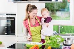 Mum kucharstwo z dzieckiem w ręce Fotografia Royalty Free