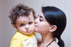 Mum kust de zoon op een wang, kijkt de jongen in le Stock Afbeelding
