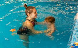 Mum learns kid to float in pool Stock Photos