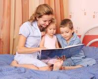 Mum leest het boek aan de kinderen royalty-vrije stock afbeeldingen