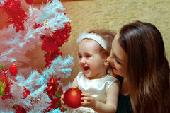 Mum with a little daughter decorate a Christmas tree and having Stock Photos