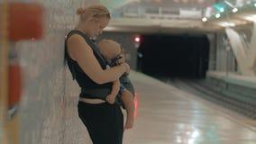 Mum med att sova behandla som ett barn det väntande på drevet i tunnelbana arkivfilmer