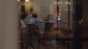 Mum med sonen på tabellen som reflekterar i fönstret på natten stock video