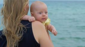 Mum met babydochter die van overzees en wind genieten stock footage