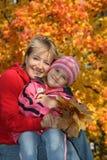 Mum met een dochter in de herfstpark Royalty-vrije Stock Afbeelding